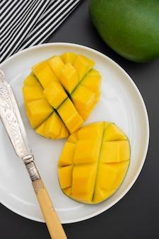 Tranches de mangue sur une assiette ronde blanche prête à être servie