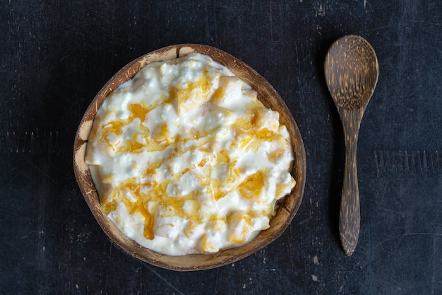 Tranches de mangue jaune sucrée mûre avec du fromage cottage blanc, du miel et de la crème sure dans un bol de noix de coco, gros plan