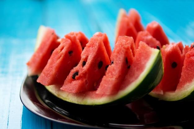 Tranches de melon d'eau fraîche sur un fond bleu