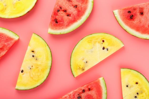 Tranches de melon d'eau rouge et jaune sur un rose dans la forme. idée de nourriture minimale