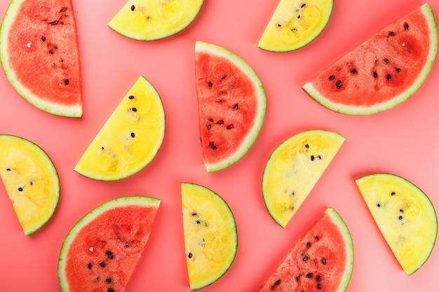 Tranches de melon d'eau rouge et jaune sur rose