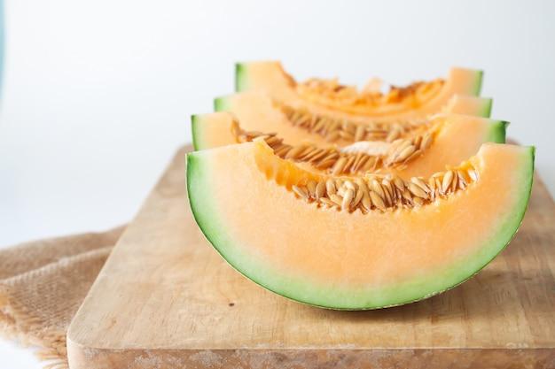 Tranches de melons japonais sur une planche à découper en bois sur fond blanc