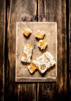 Tranches de miel naturel dans le peigne sur la planche. sur fond de bois.