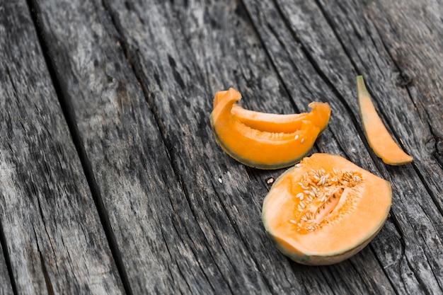 Tranches et moitié de melon musqué sur une vieille table en bois