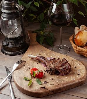 Tranches de morceau de steak d'agneau sur os avec des paillettes de sel de mer, sur une planche de bois