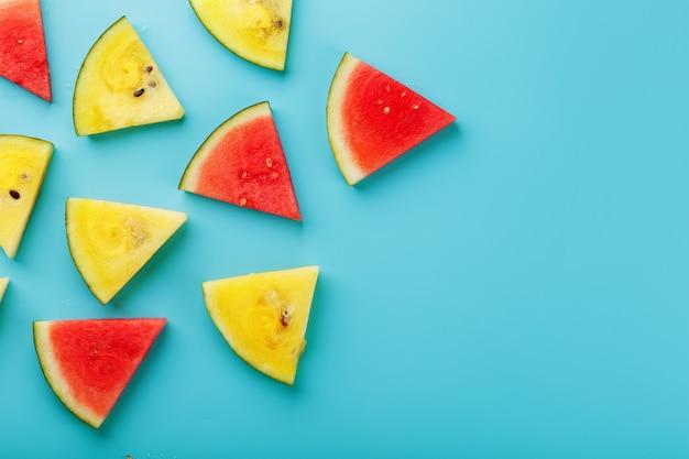 Tranches de morceaux frais de melon d'eau jaune et rouge sur un bleu. place libre.