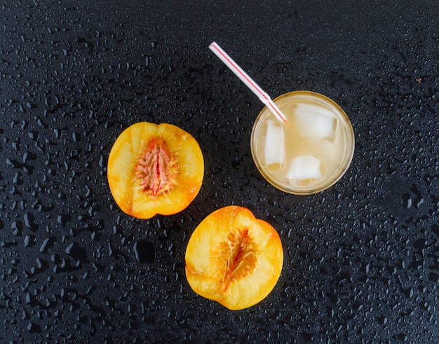 Tranches de nectarine avec du jus glacé à plat sur une surface gris foncé