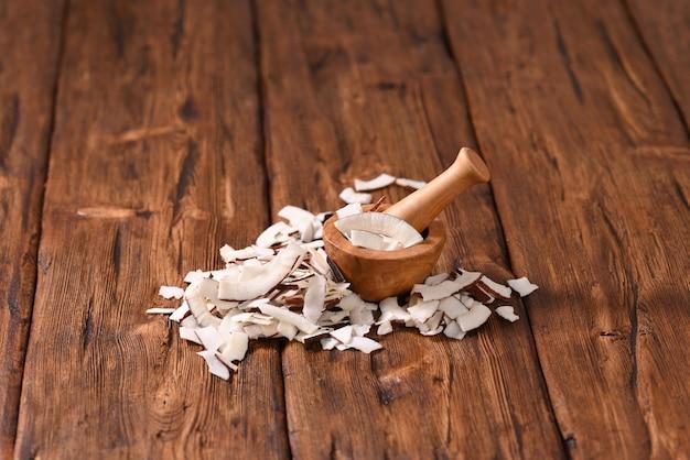 Tranches de noix de coco avec la peau écrasée dans un mortier d'épices
