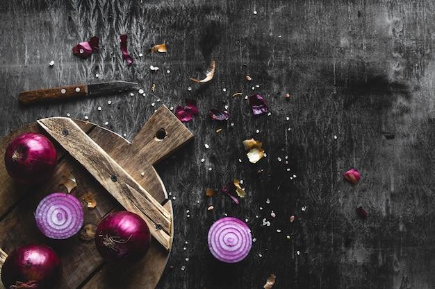 Tranches d'oignon rouge sur planche de bois avec dark