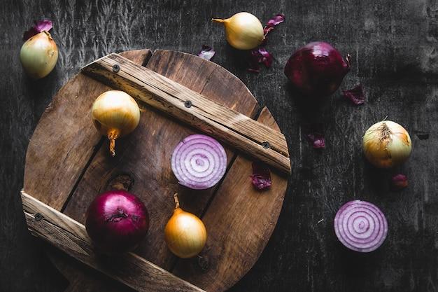 Tranches d'oignon rouge sur planche de bois avec fond sombre