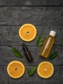 Tranches d'orange, une bouteille médicale et une bouteille de jus sur un fond en bois.