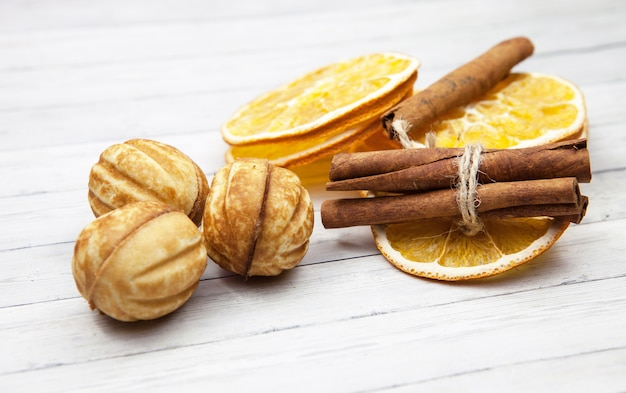 Tranches d'orange à la cannelle et des biscuits sur un fond en bois clair