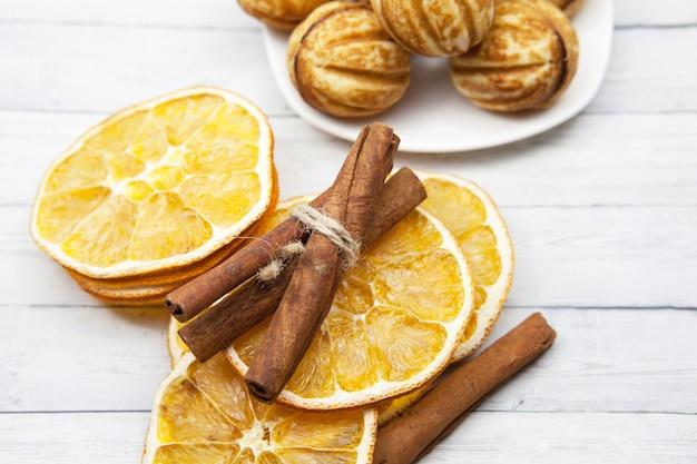 Tranches d'orange à la cannelle et des biscuits sur fond en bois, vue de dessus