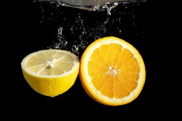Tranches d'orange et de citron frais dans les éclaboussures d'eau isolé sur fond noir.