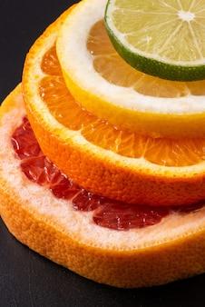 Tranches d'orange, citron, pamplemousse et citron vert sur fond noir