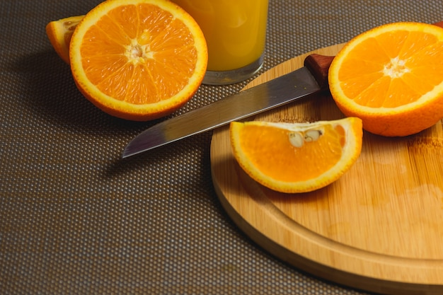 Tranches d'orange avec un couteau sur une planche à découper en bois