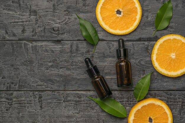 Tranches d'orange et deux bouteilles avec pipettes sur un fond en bois. place pour le texte.
