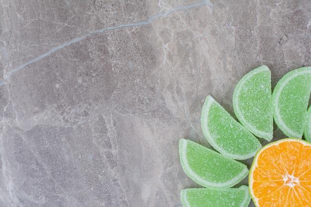 Tranches d'orange fraîches avec des marmelades sucrées sur fond de marbre.