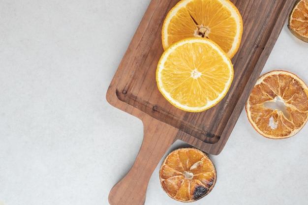 Tranches d'orange fraîches et séchées sur planche de bois