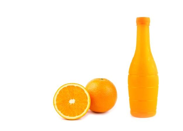Tranches d'orange, jus d'orange en bouteille sur fond blanc.