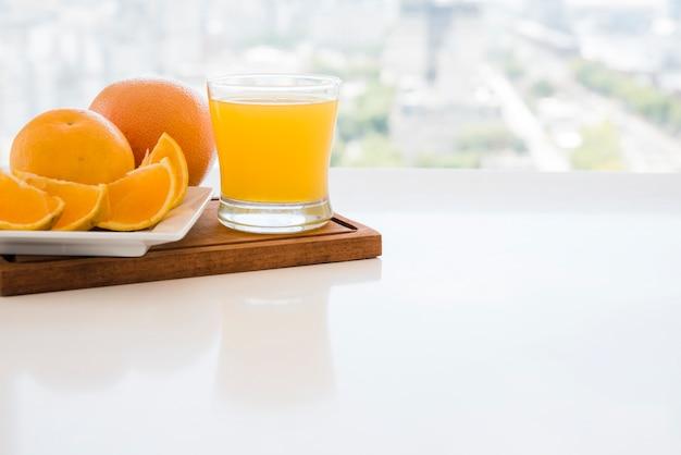 Tranches d'orange et jus sur une planche à découper sur la table blanche