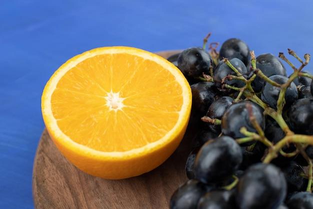 Tranches d'orange avec des raisins sur planche de bois
