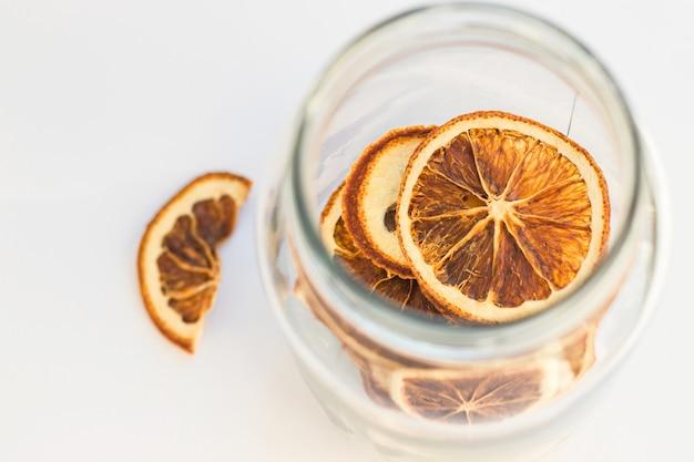 Tranches d'orange séchées naturelles dans un bocal en verre. collation saine. décorations de noël et du nouvel an. vue de dessus.