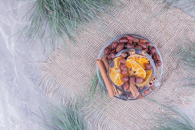 Tranches d'orange sèches avec de la cannelle et des hanches dans une tasse en verre