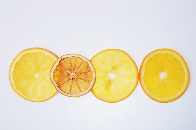 Tranches d'orange translucides sur fond blanc, tranches sèches et mûres ensemble 1
