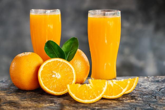 Tranches d'orange et verres de jus d'orange sur la table