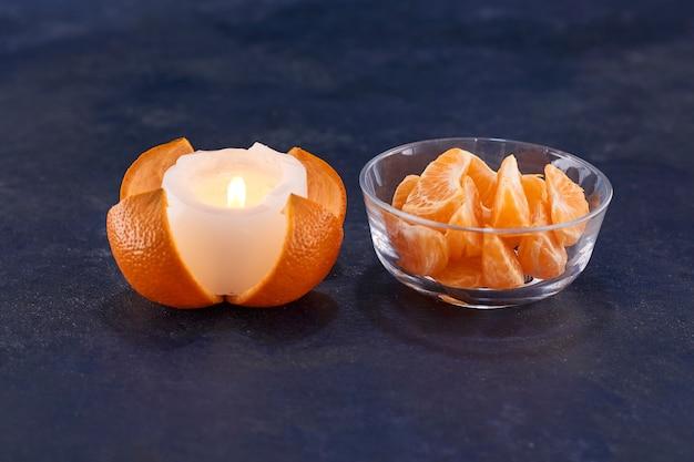 Tranches d'oranges et bougie fondue sur une surface grise