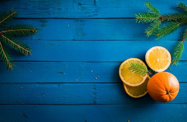 Tranches d'oranges décorées avec sapin sur fond en bois bleu