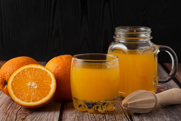 Tranches d'oranges avec du jus dans le bocal en verre et la tasse