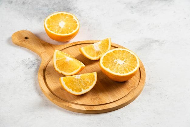 Tranches d'oranges fraîches avec alésoir en bois sur marbre.