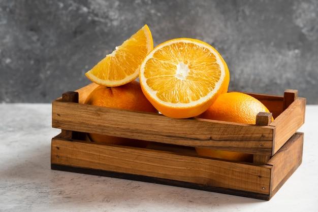 Tranches d'oranges fraîches sur marbre.