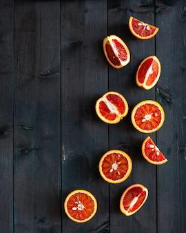 Tranches d'oranges rouges siciliennes mûres sur fond de bois foncé, flatlay