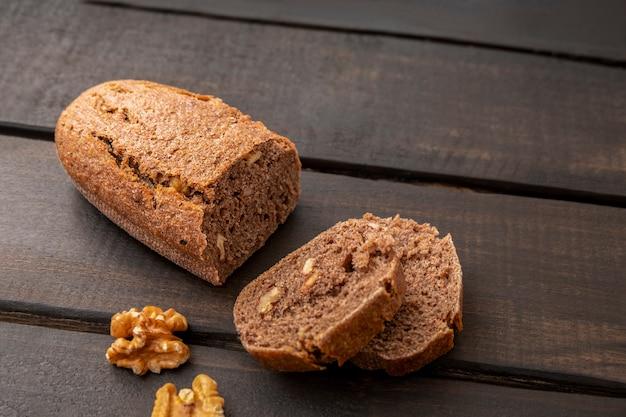 Tranches de pain au levain aux noix sur fond de bois foncé avec espace de copie