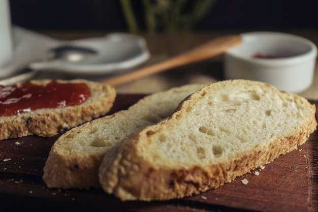 Tranches de pain au premier plan avec une tranche de confiture à tartiner. vue à 45 degrés.