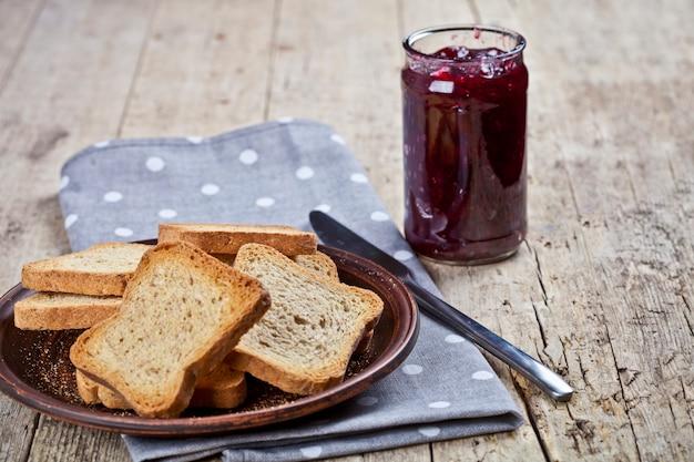 Tranches de pain aux céréales grillées sur une assiette grise et pot avec confiture de cerises faite maison