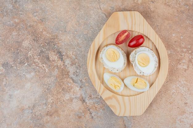 Tranches de pain aux œufs durs et tomate sur plaque en bois