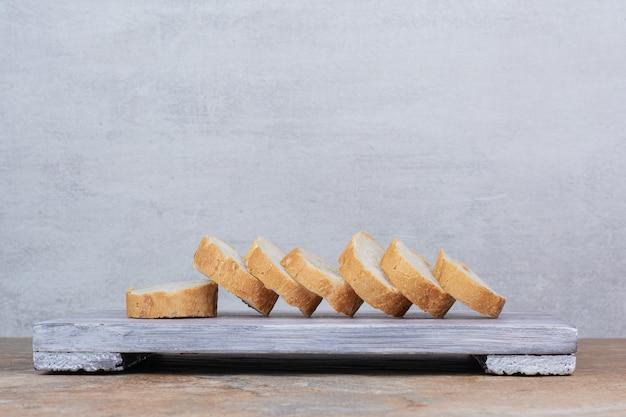 Tranches de pain baguette sur planche de bois