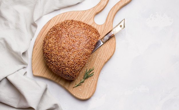 Tranches de pain blanc aux graines de sésame sur une planche de bois. copie espace