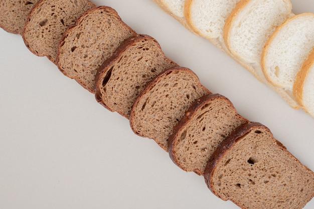 Tranches de pain blanc et brun frais sur une surface blanche