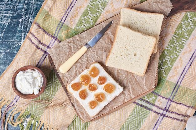 Tranches de pain blanc avec crème sure et confiture.