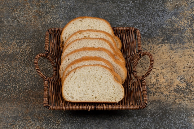Tranches de pain blanc frais dans un panier en bois
