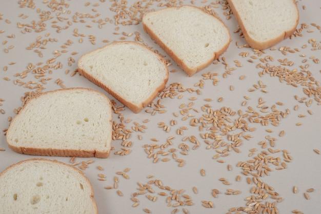 Tranches de pain blanc frais avec des grains d'avoine sur une surface blanche