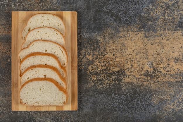 Tranches de pain blanc sur planche de bois