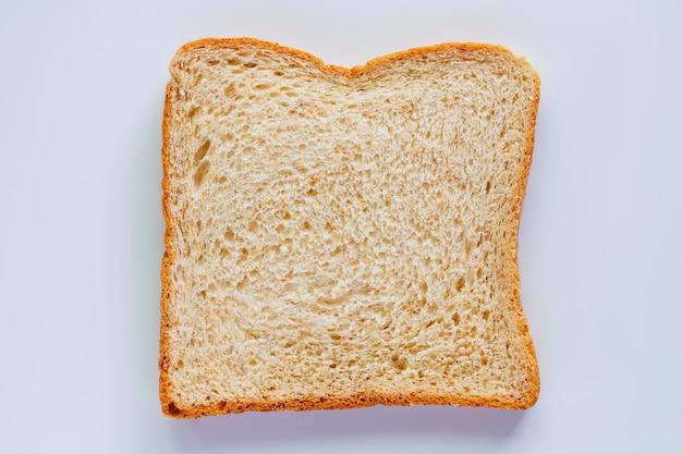 Tranches de pain de blé entier fin sur fond blanc