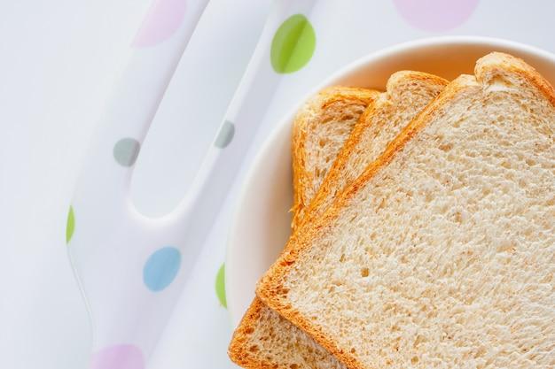 Tranches de pain de blé entier fin sur plaque