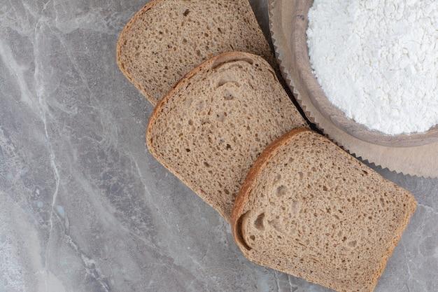 Tranches de pain brun avec de la farine sur une surface en marbre